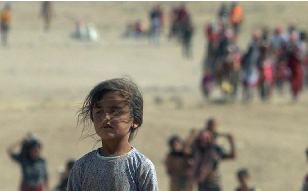 Nena en un paisatge de guerra.